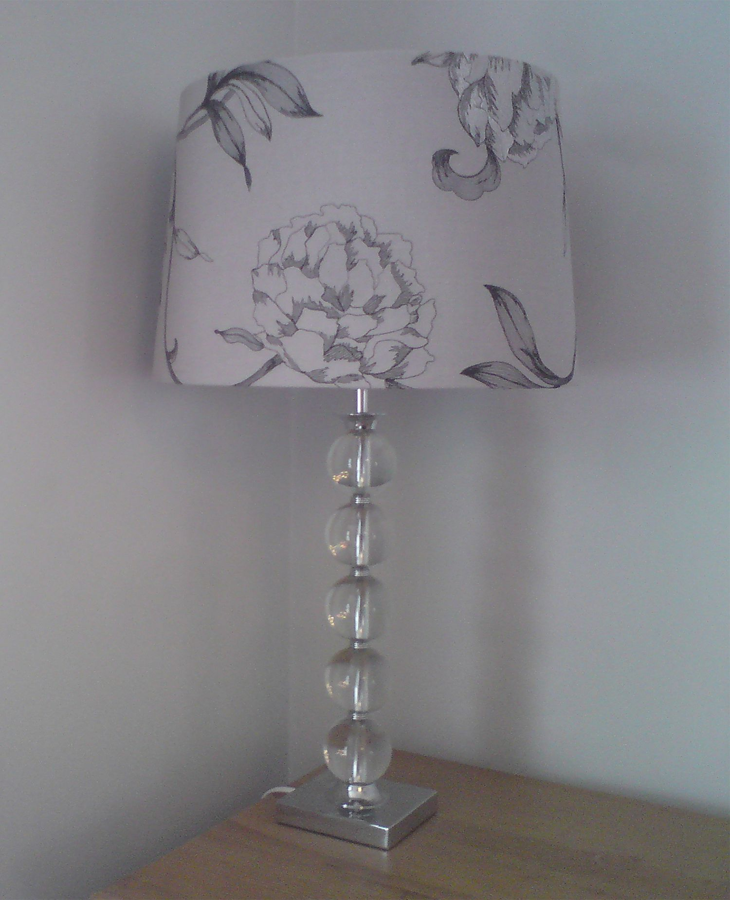 The old glass table lamp with a grey lampshade, on top of the pine chest of drawers.
