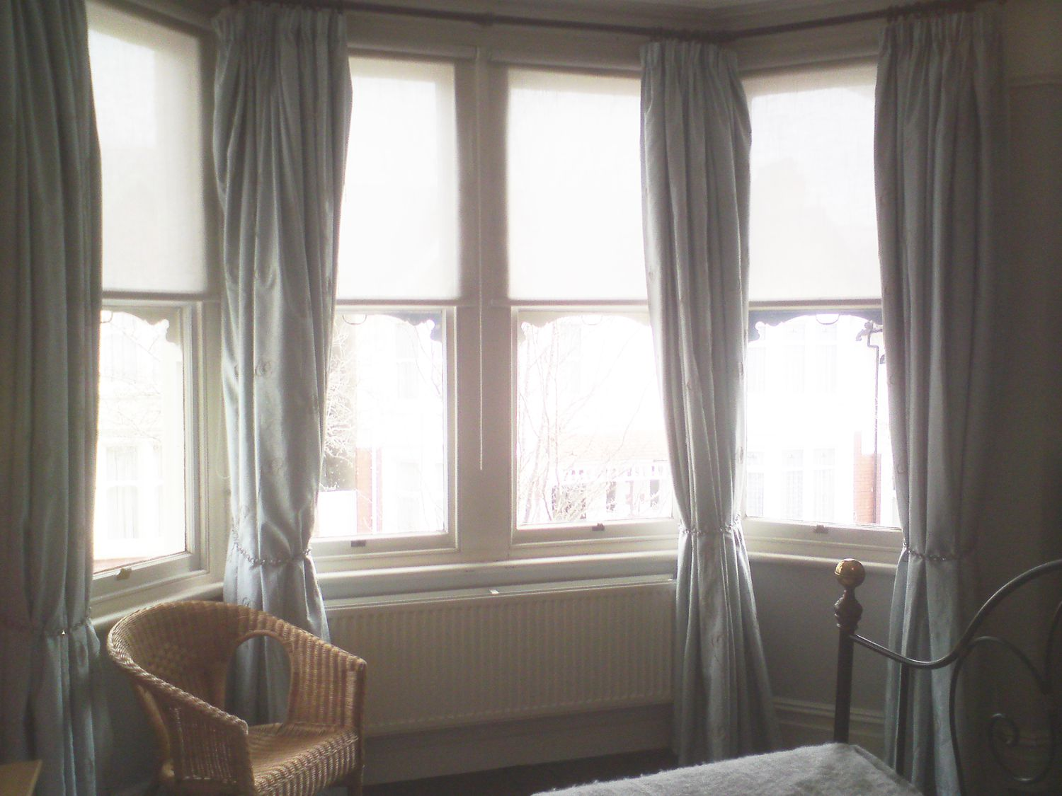 A view of the window with the original four curtains looking messy.