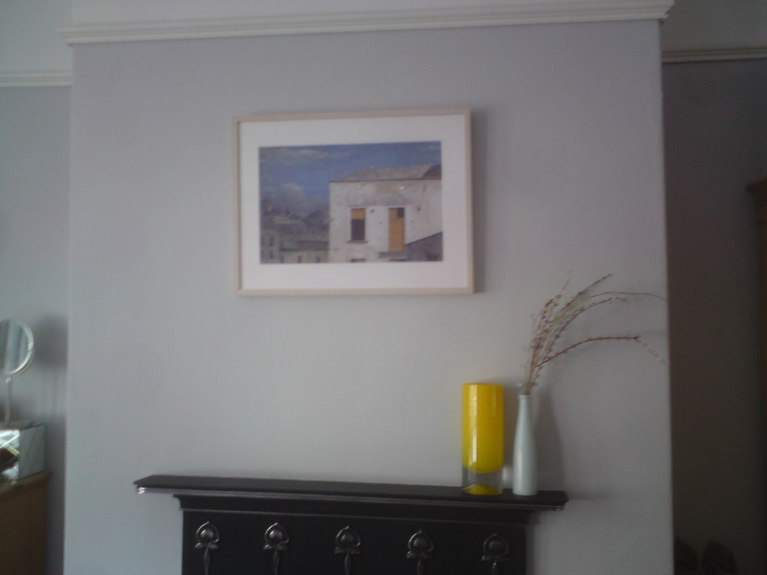 Before, the walls were grey and there were blue and yellow vases on the mantle piece.