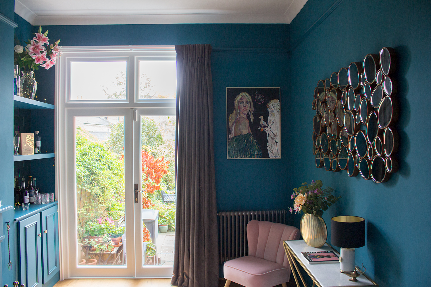 A photo of a living room painted in a blue with a strong green undertone, to keep it warm