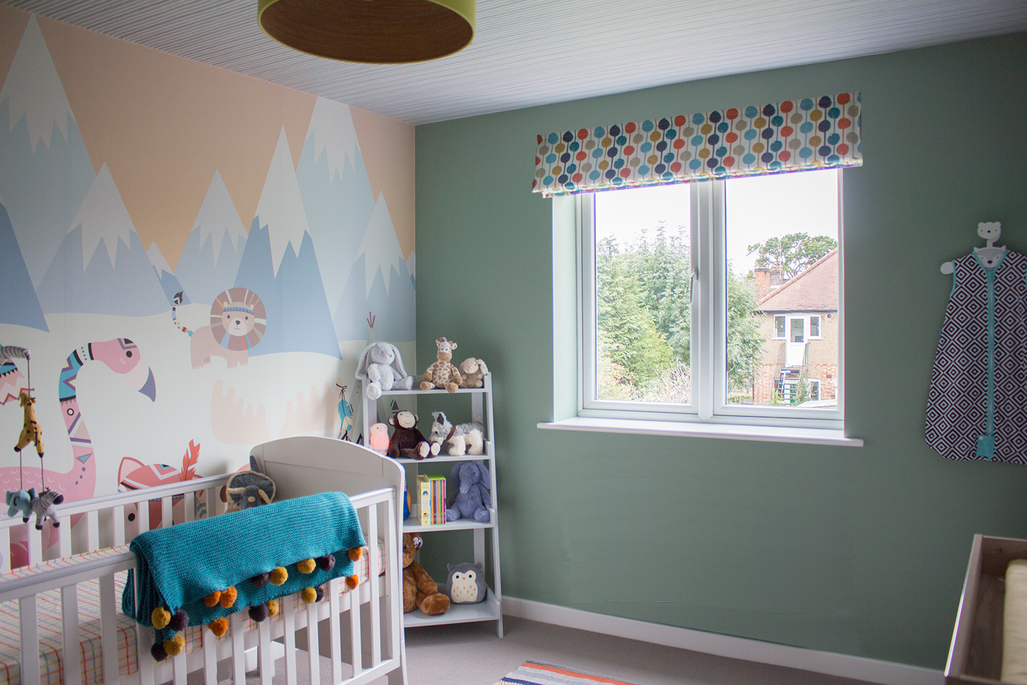 A photo of the new nursery with wallpaper mural