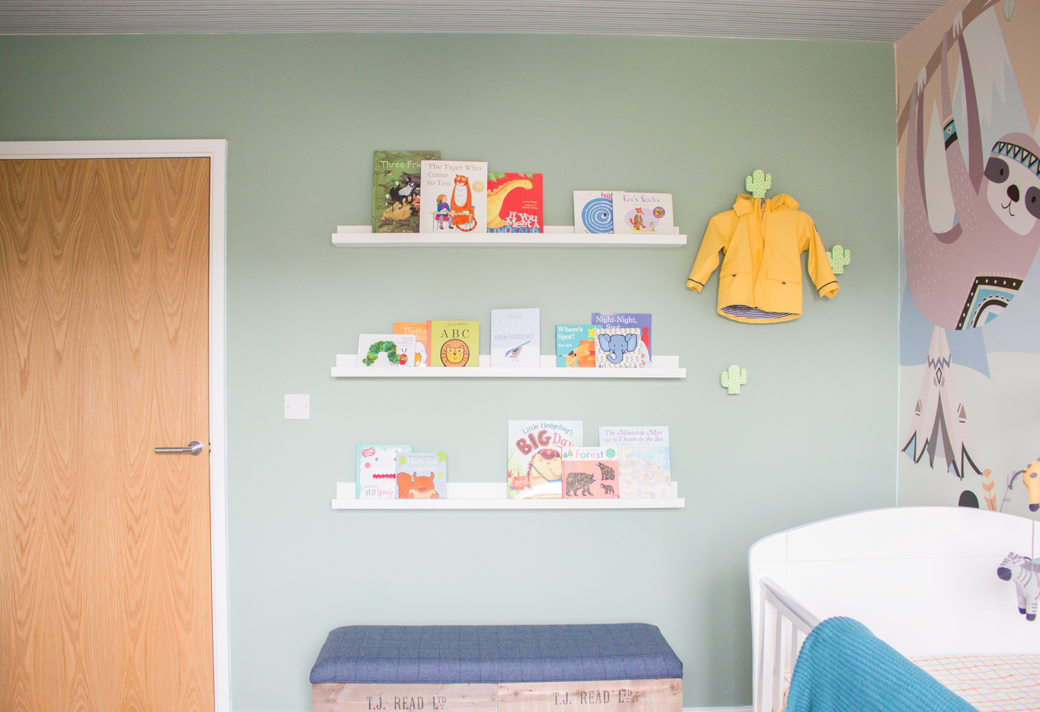 A photo of the new nursery with rows of colourful books on picture shelves.