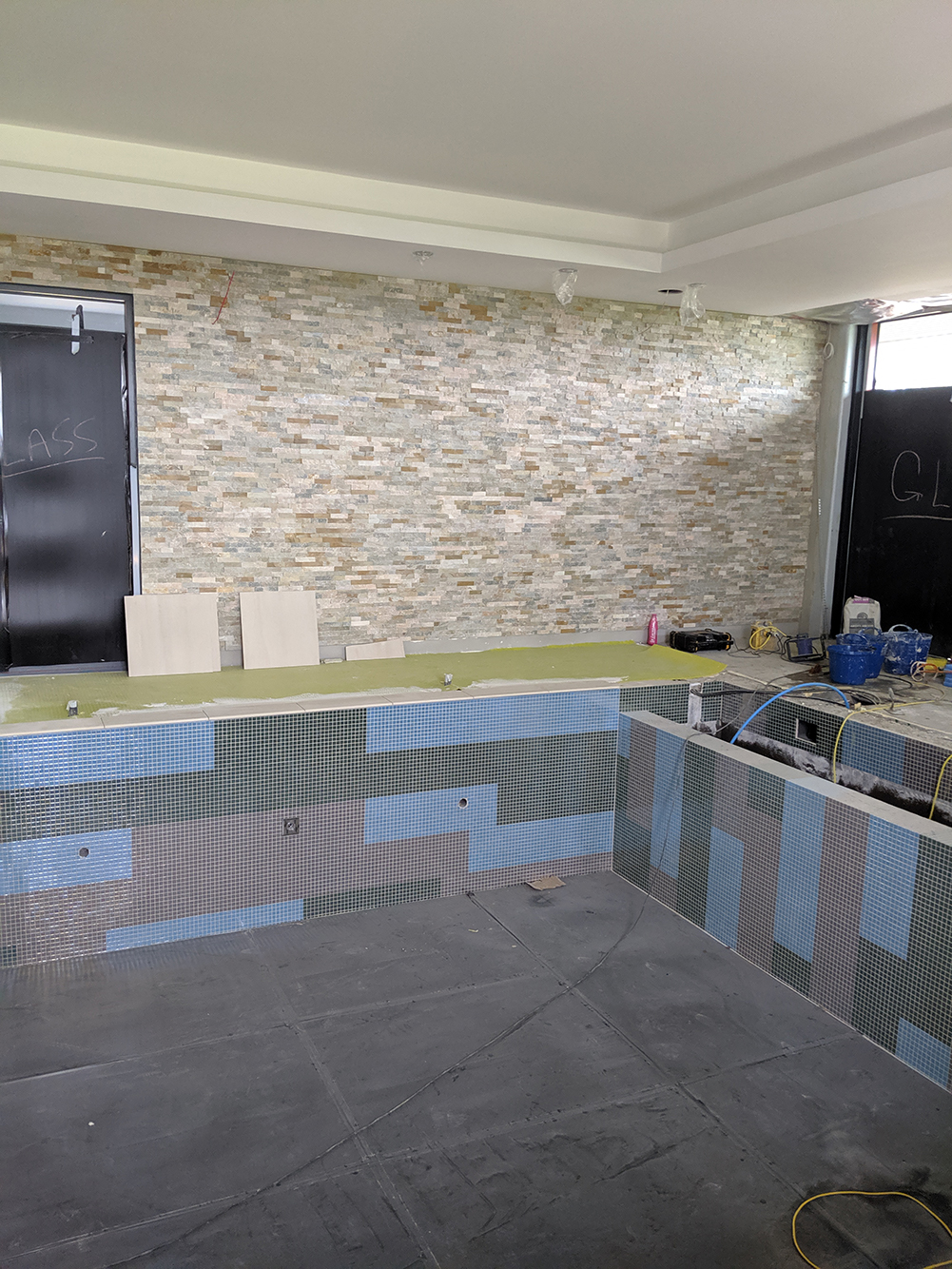 A photo showing the split face tile on the wall, with the pool and floor tiles with it.