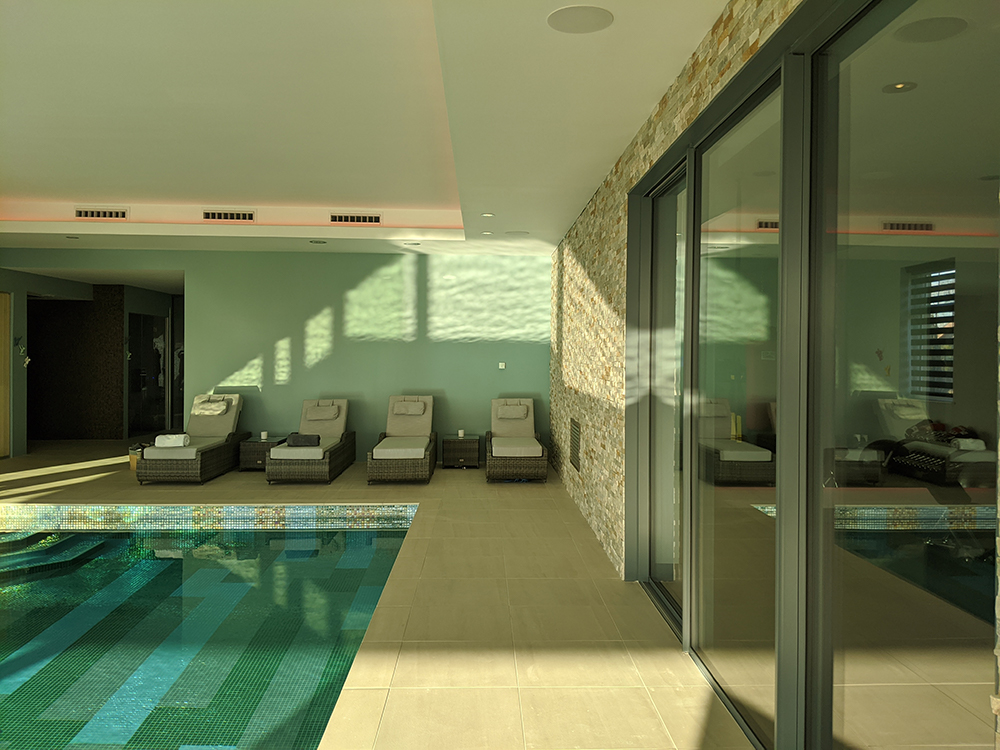 A photo of the finished pool area, with four sunloungers lined up ready to relax on.