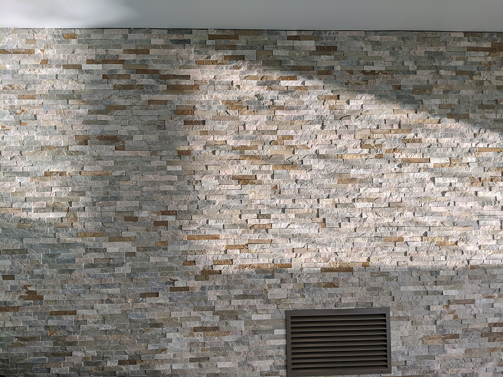 A photo of the newly tiled wall with the painted ventilation grille.