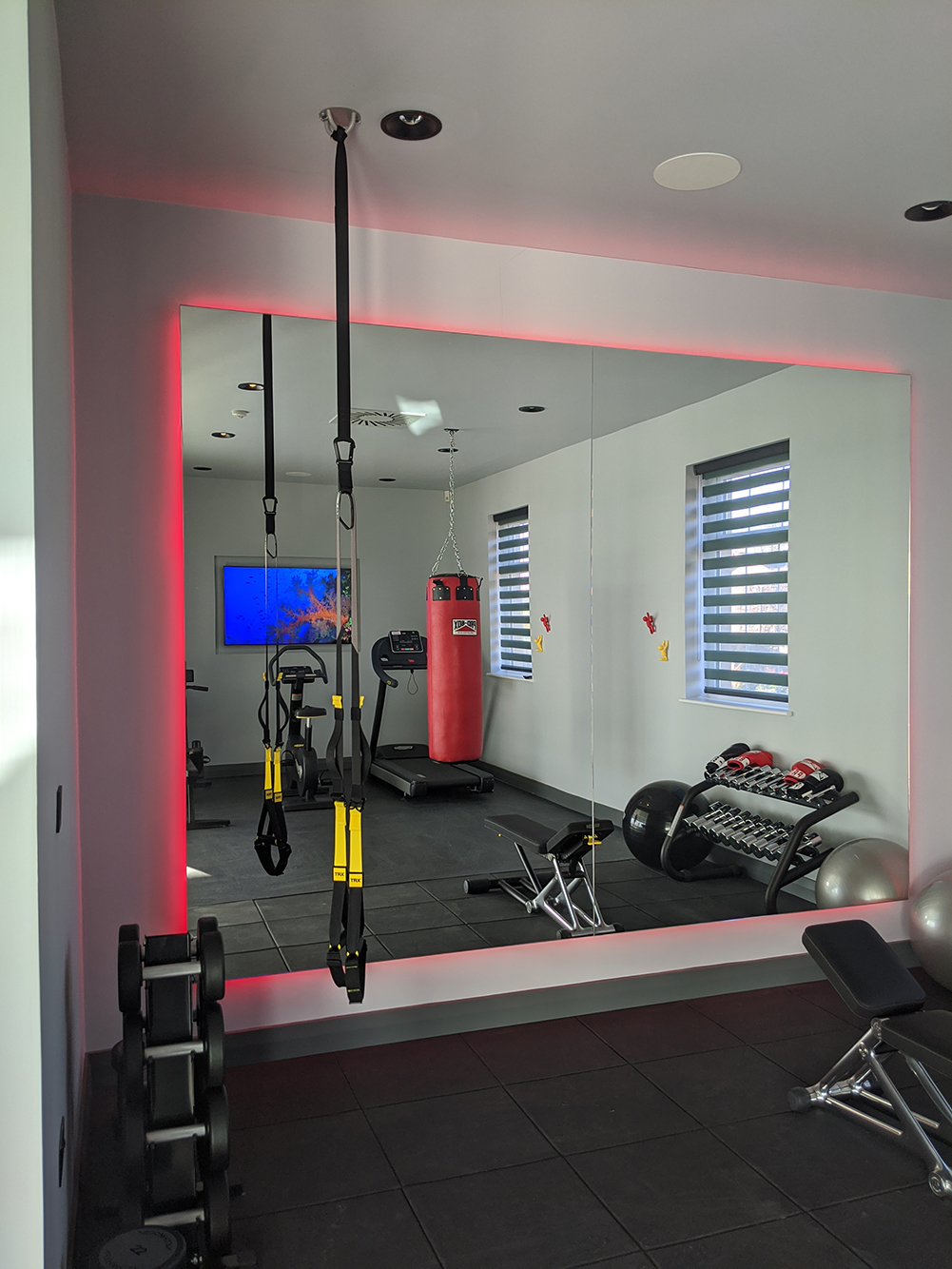 A photo of the finished gym with red LED lighting around the mirror.