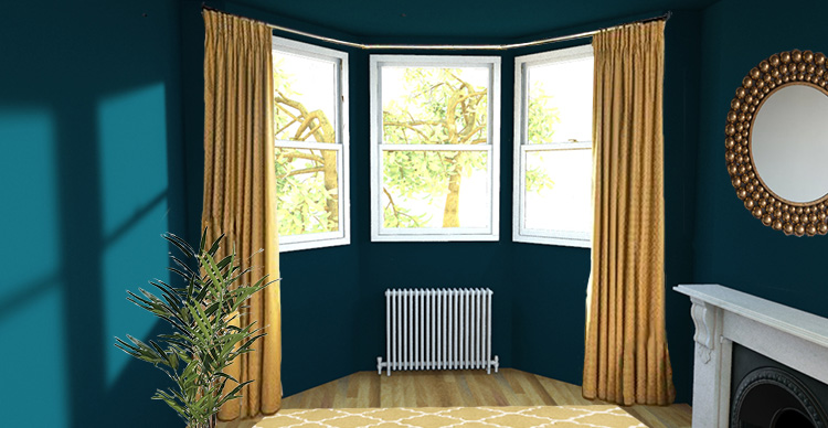 A picture of a bay window with a pair of floor length curtains