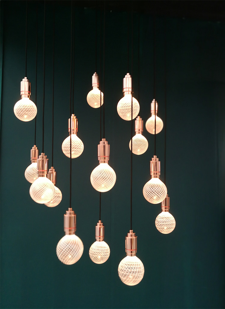 a photo of a very dark green wall with a brass light fitting with many bulbs in front of it.