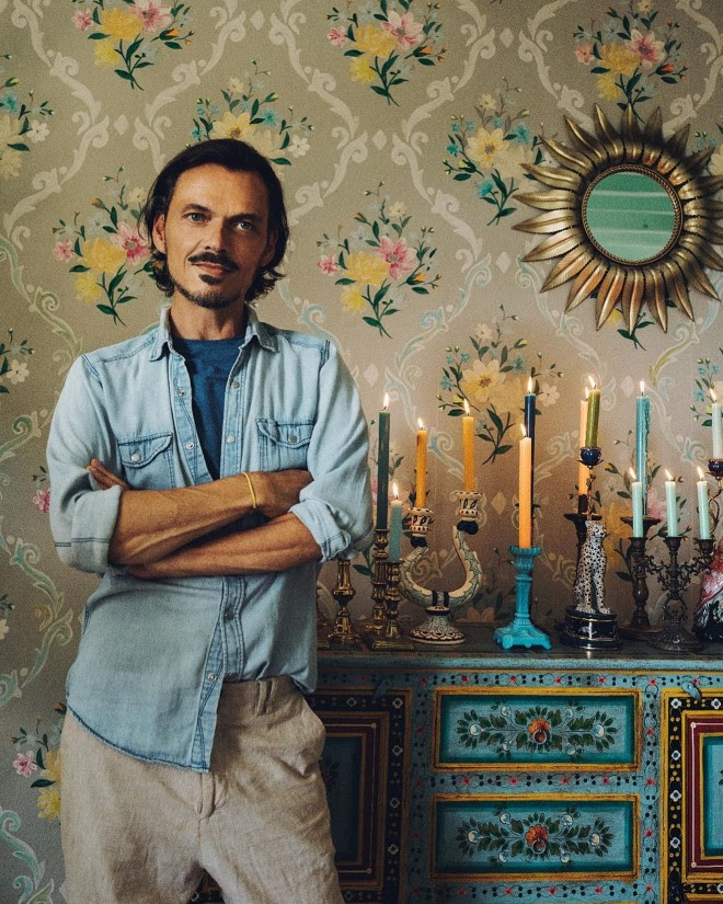 A picture of designer Matthew Williamson, standing next to a blue dresser with a wide array of candles and candlesticks on the top. Behind him in a ornate floral wallpaper with a sunburst mirror