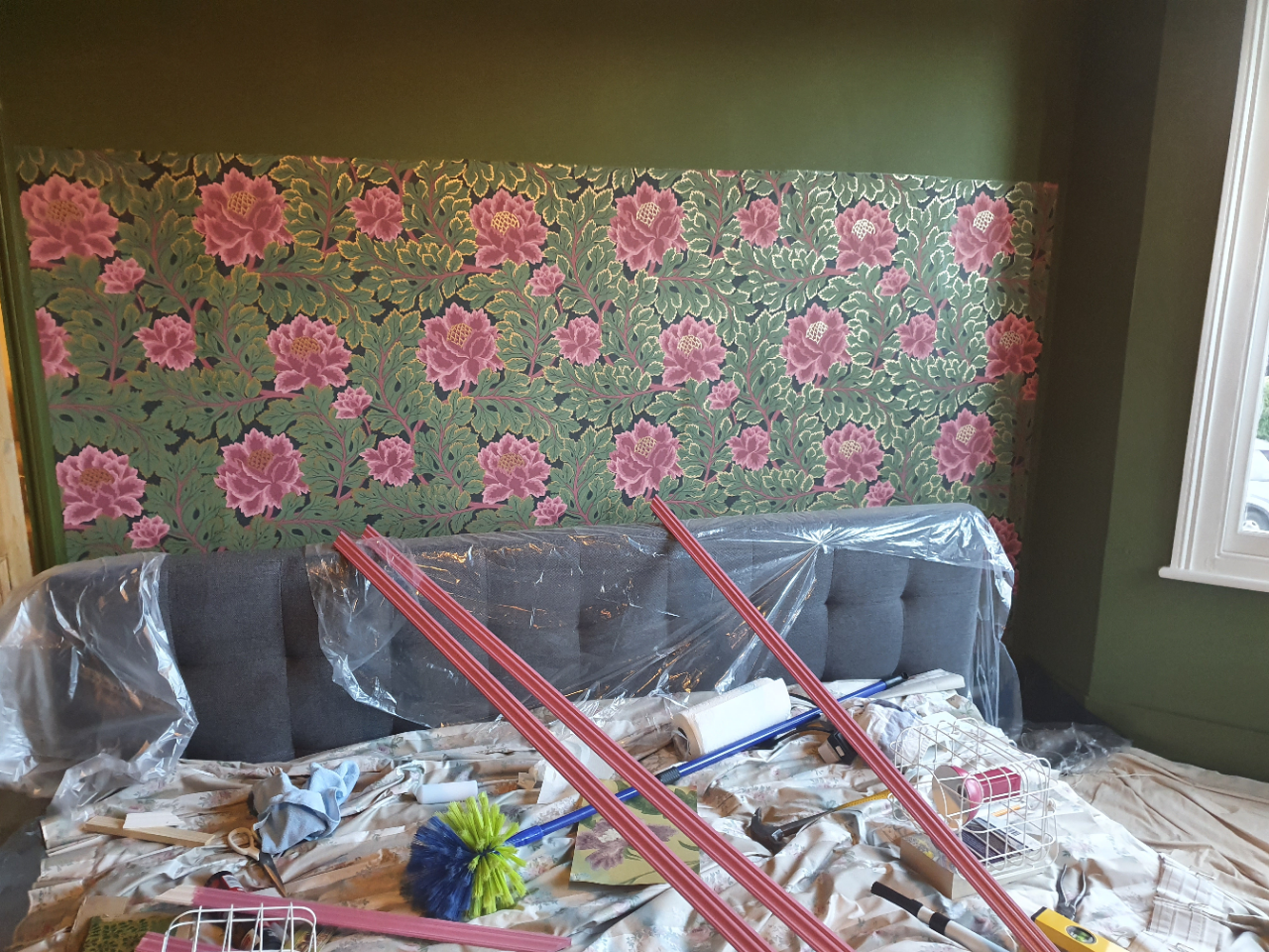 A photo of the wallpaper on the wall, with the pink beading on the bed ready to go up.