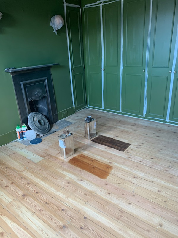 A photo of the sanded floorboards with two varnish colour options
