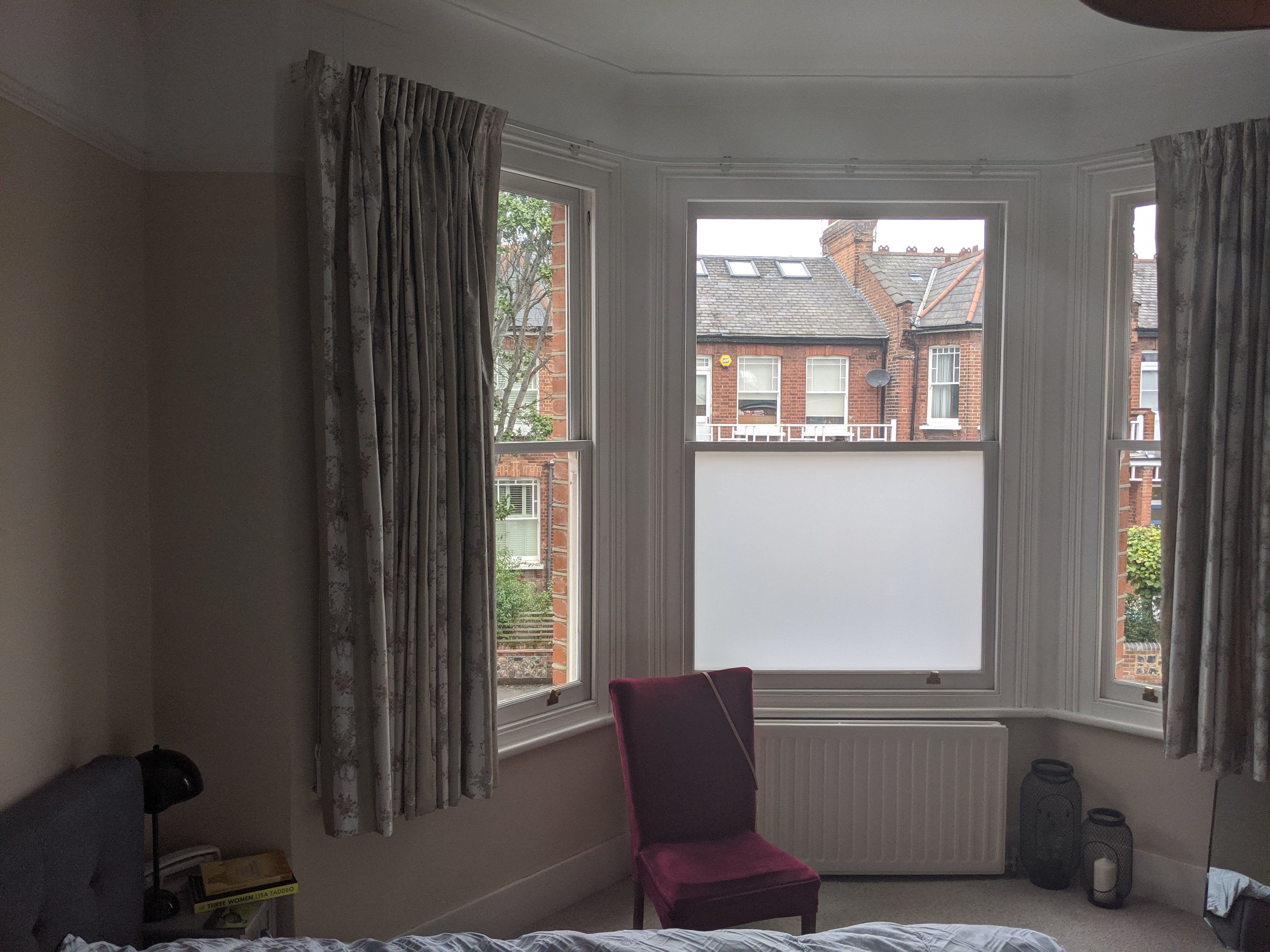A before photo of the room, showing the peach walls and floral curtains at the window.