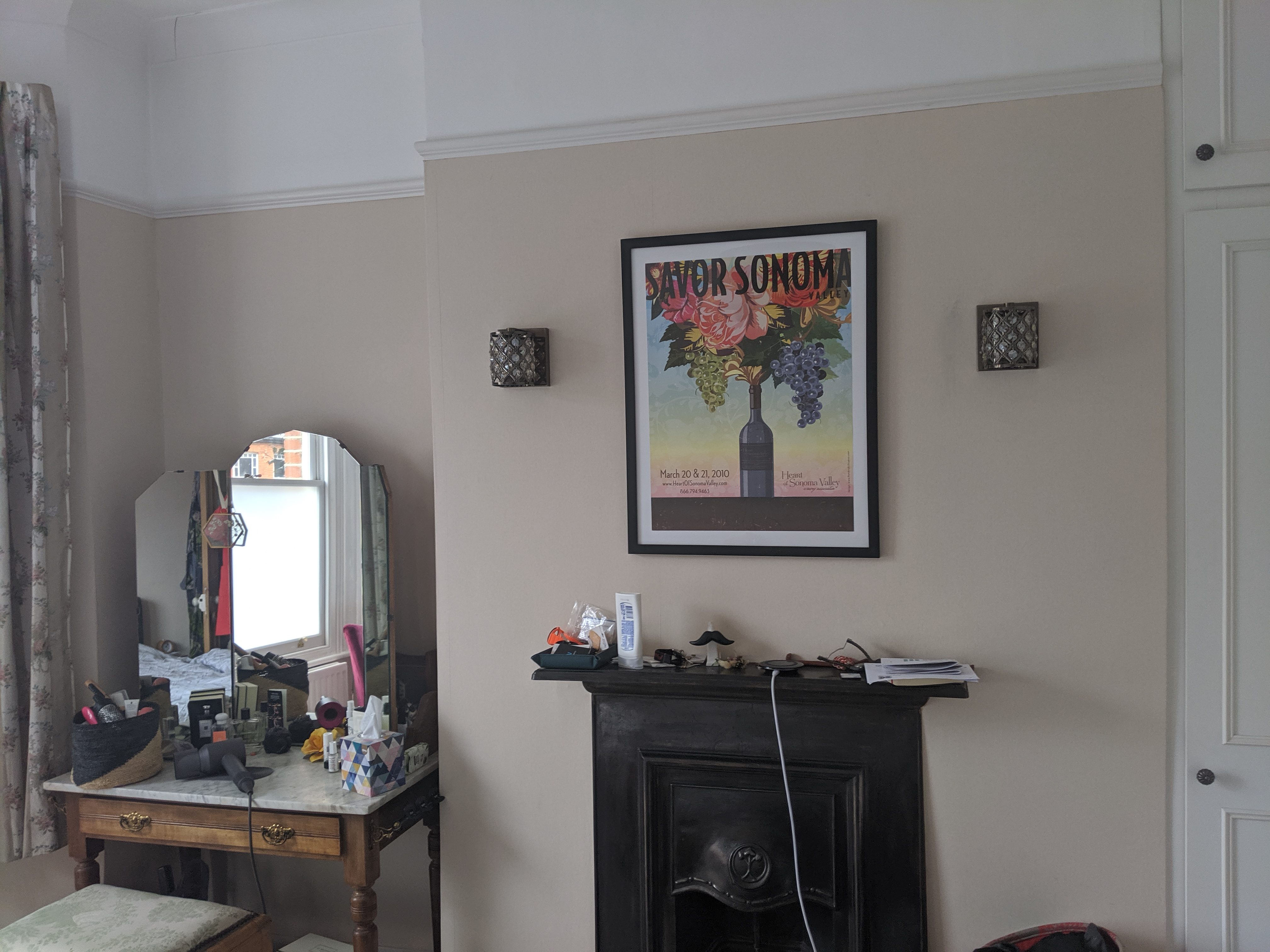 A photo of the room before, with the original fireplace and the old wall lights.