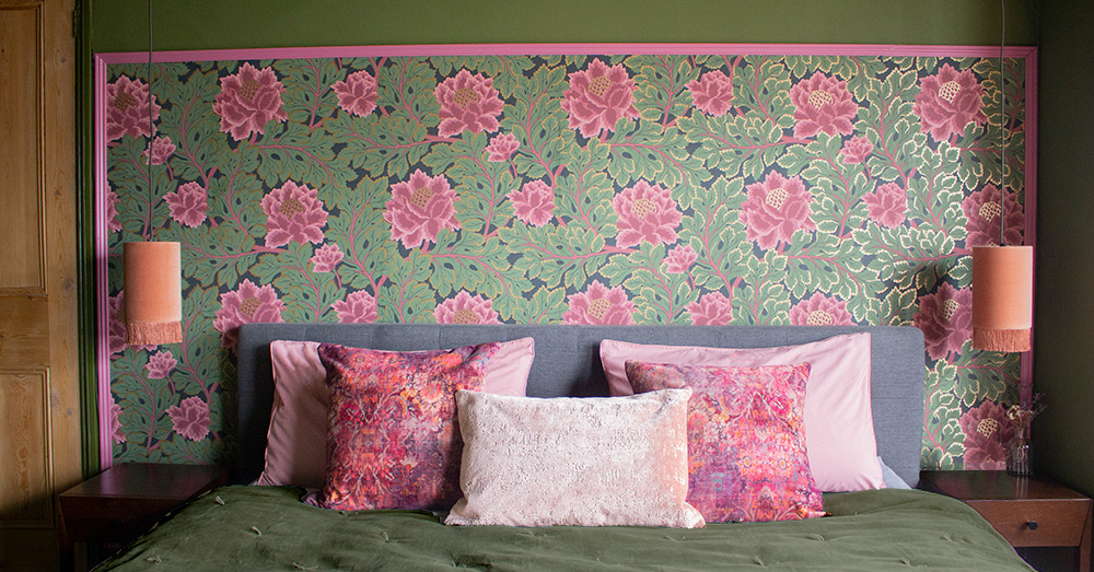 A close up of the bed with pink and green wallpaper behind and dark green walls.