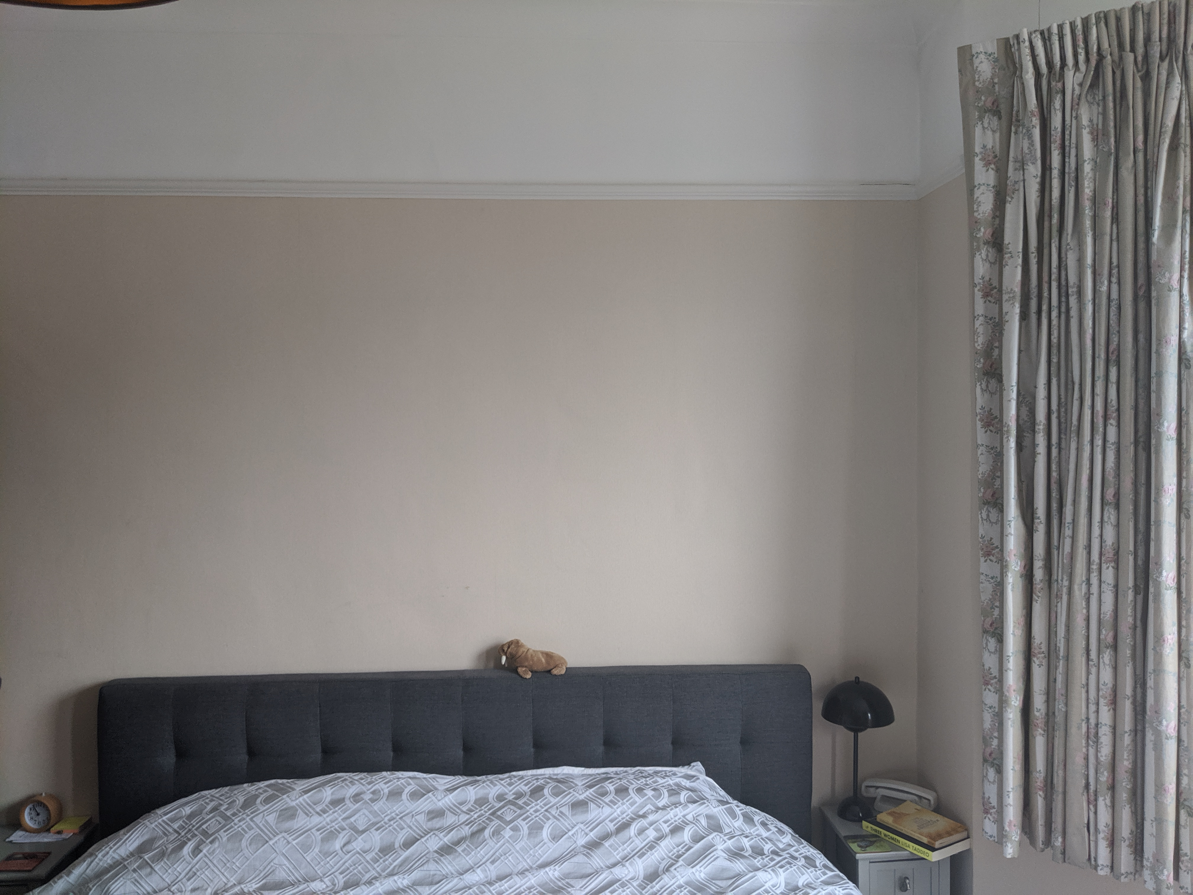 A photo of the room before, showing the bed  against a plain wall.