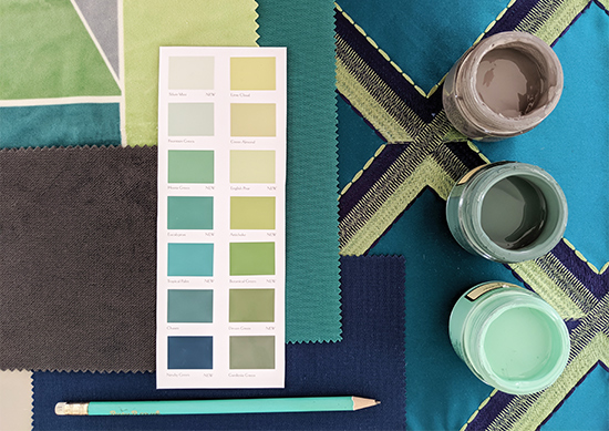 A selection of paints, fabrics and a paint chart arranged together.