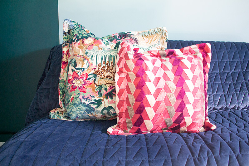 A close up of some colourful cushions on a sofa.