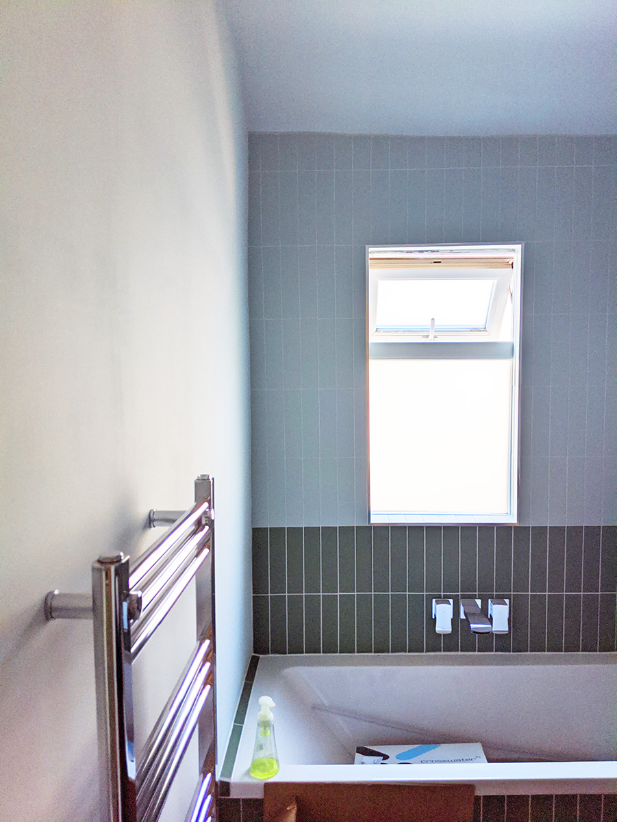 A photo of the bathroom with chrome taps and radiator.