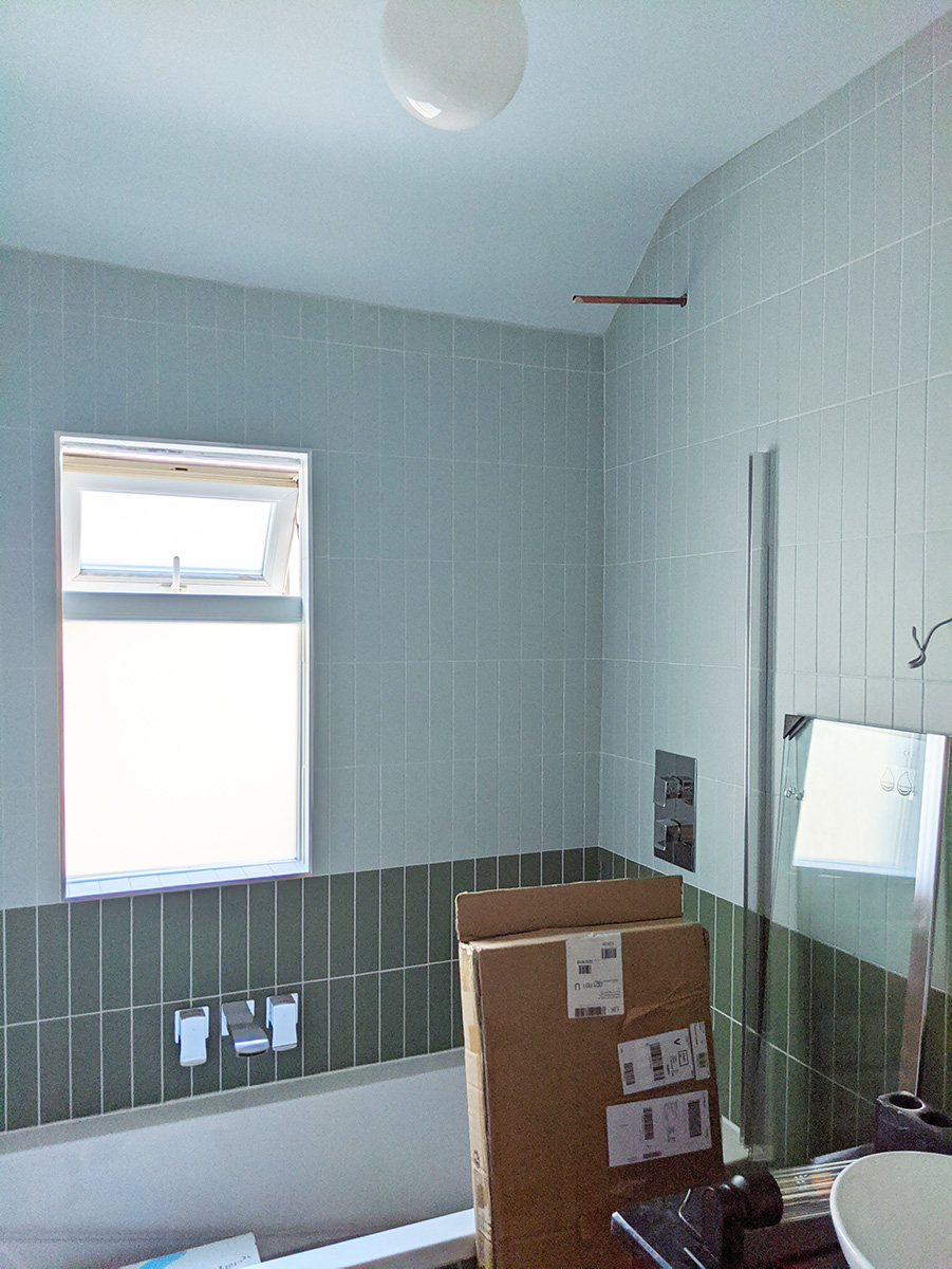 A photo of the bathroom showing the chrome taps and fittings.