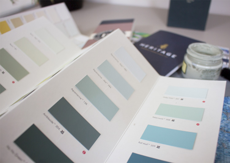 A photo of some paint charts showing mostly green paint colours.