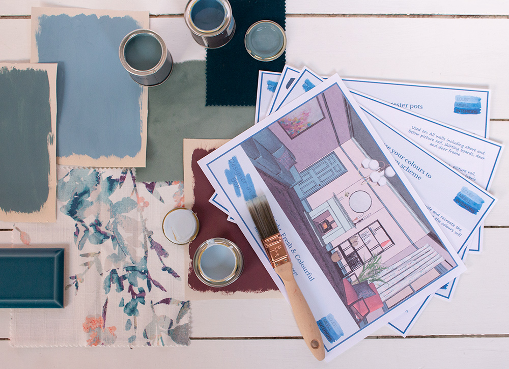 A photo of the paperwork included in Designer in a Box with paint and fabric samples around it.