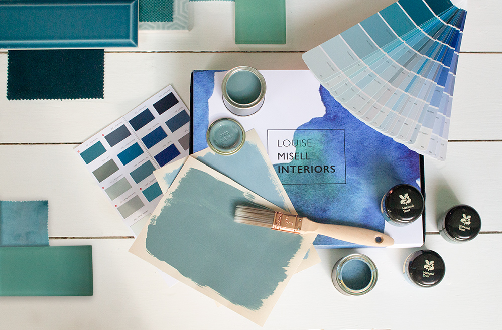 A photo of the Designer in a Box with paint and fabric samples around it.