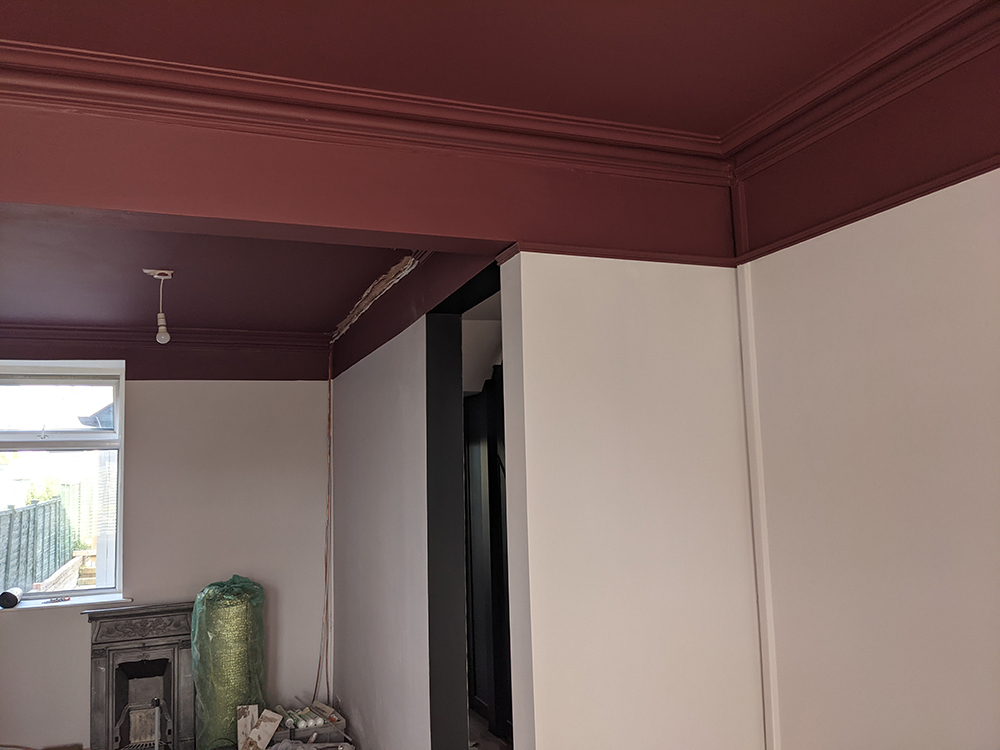 A photo of the walls showing the burgundy painted ceiling coming down to the coving.
