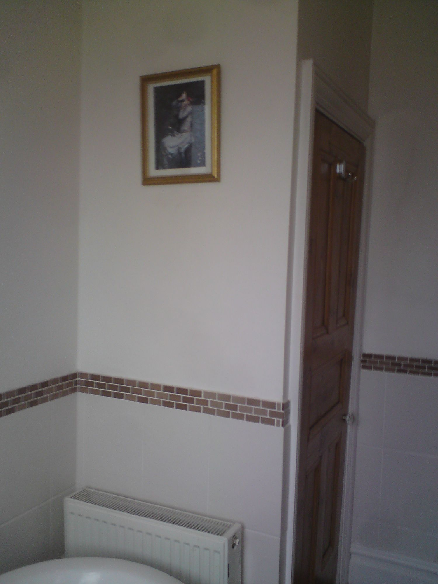 A photo of the airing cupboard door, with a bare wall where the towel radiator was moved to.