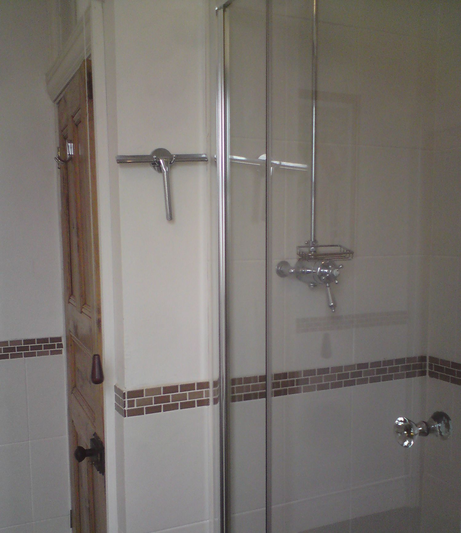 The old glass door to the shower enclosure, showing the smaller shower area.