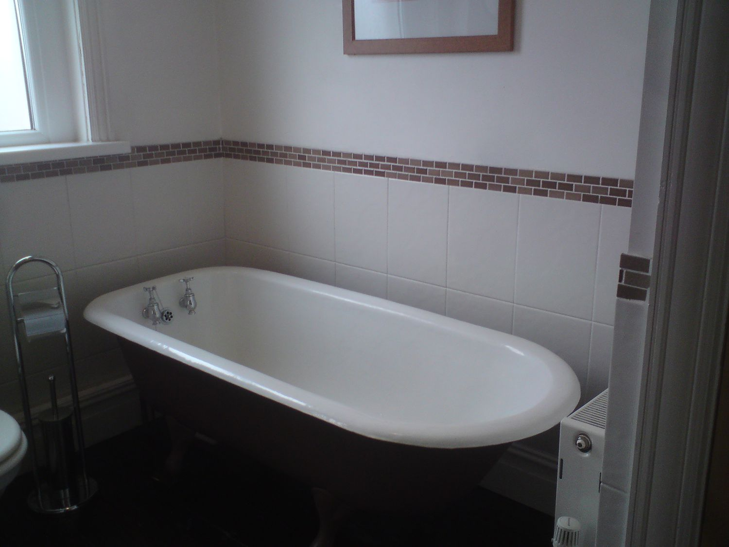 The same view of the old brown painted bath with grey tiles and brown mosaic tiles behind.