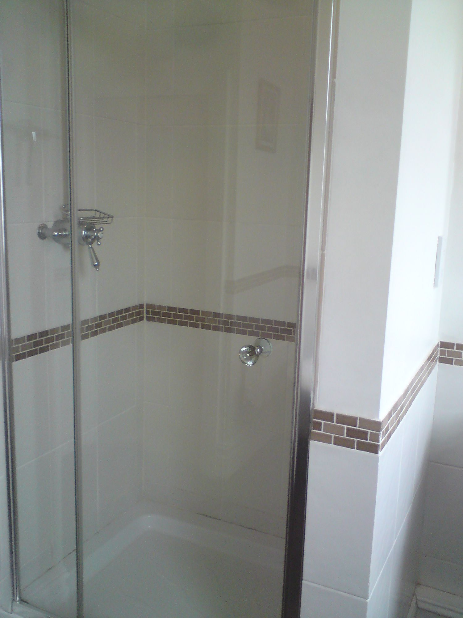 The old enclosed shower area with a glass door on a built in cubicle.