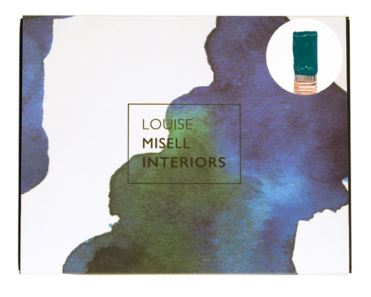 A photo of the outside of the Designer in a Box with a small paintbrush showing a dark teal paint colour.