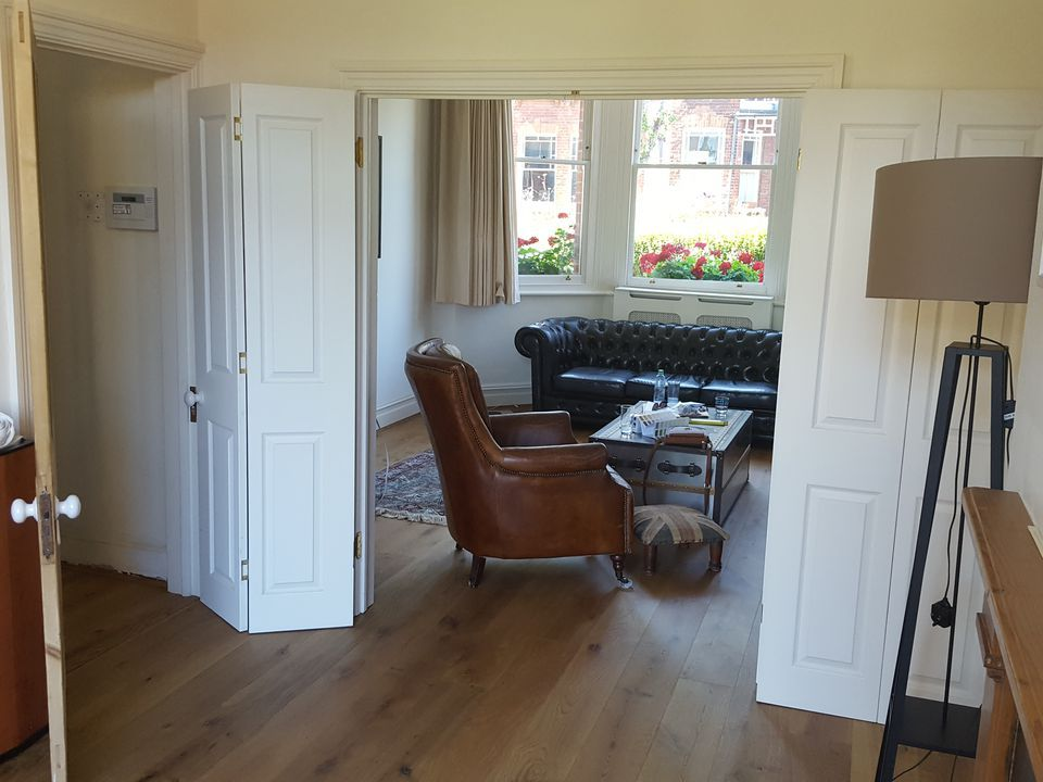 A view through the arch of the adjoining room to the cream painted room with a brown leather sofa.