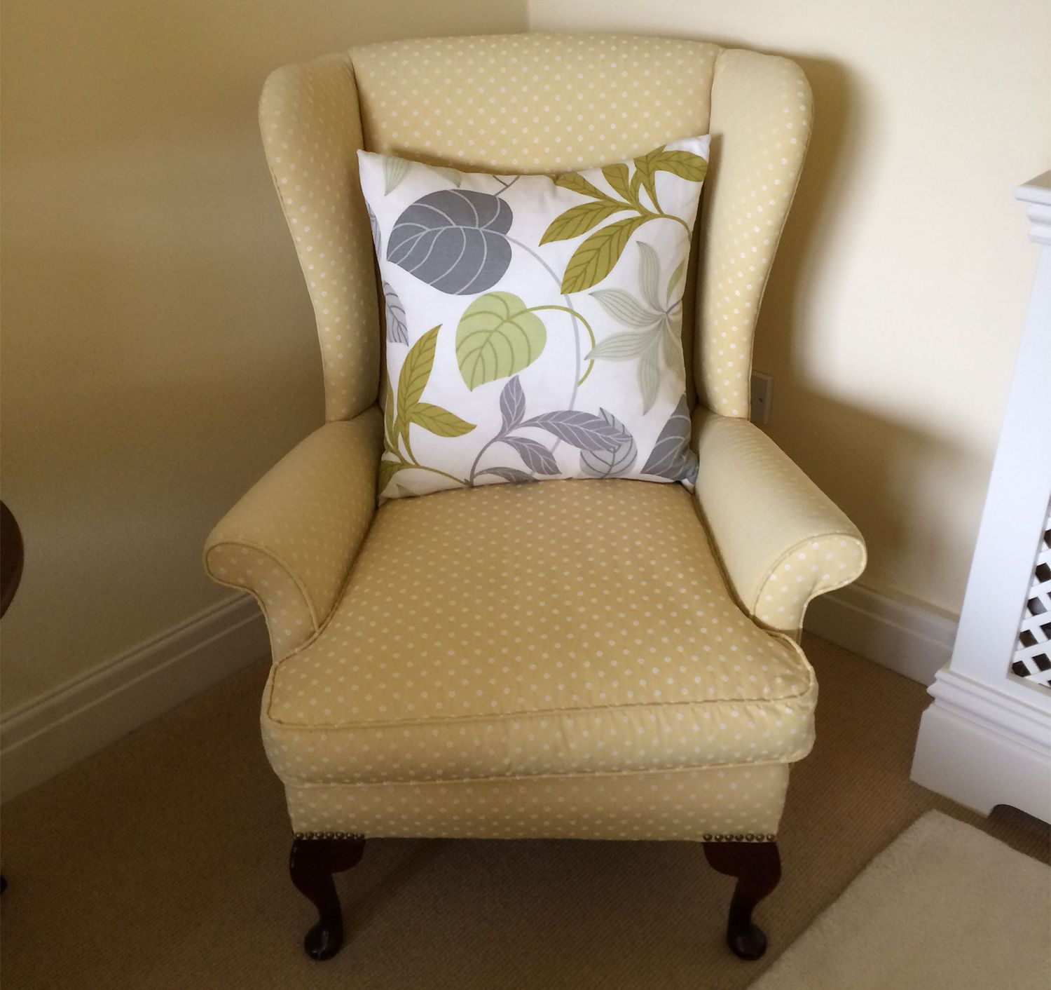 A photo of the wing chair in a yellow fabric before it was reupholstered.