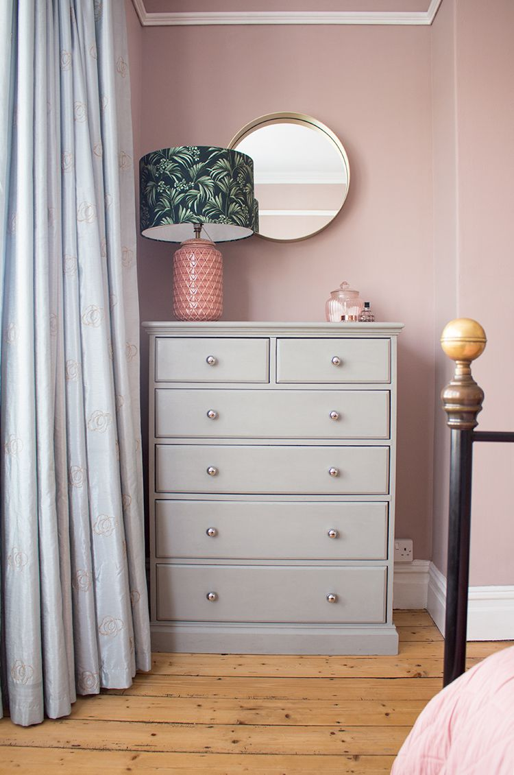 A view of the chest of drawers which has been painted grey, in front of the pink painted walls.