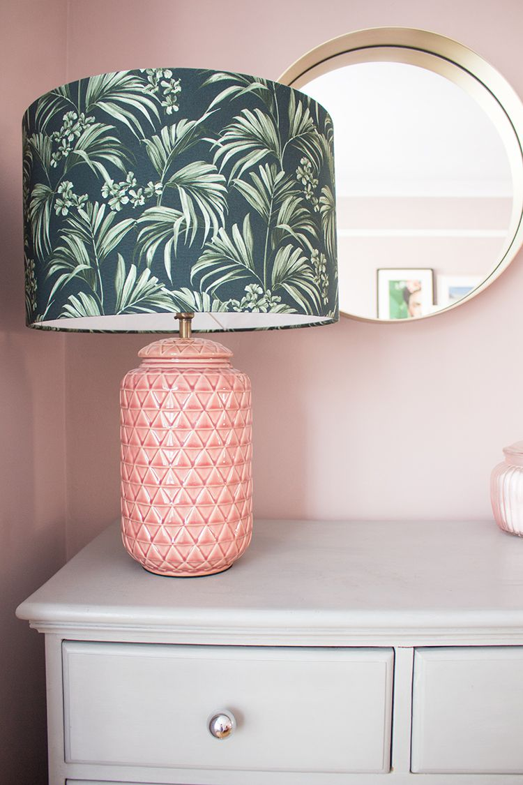 A close up of the new pink textured lamp with a green palm print lampshade on top of the grey chest of drawers.