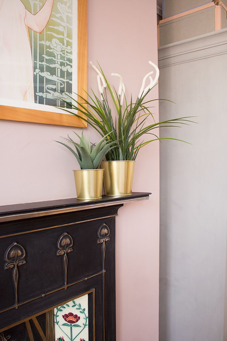 A photo of two brass plant pots with plants on the mantle piece.