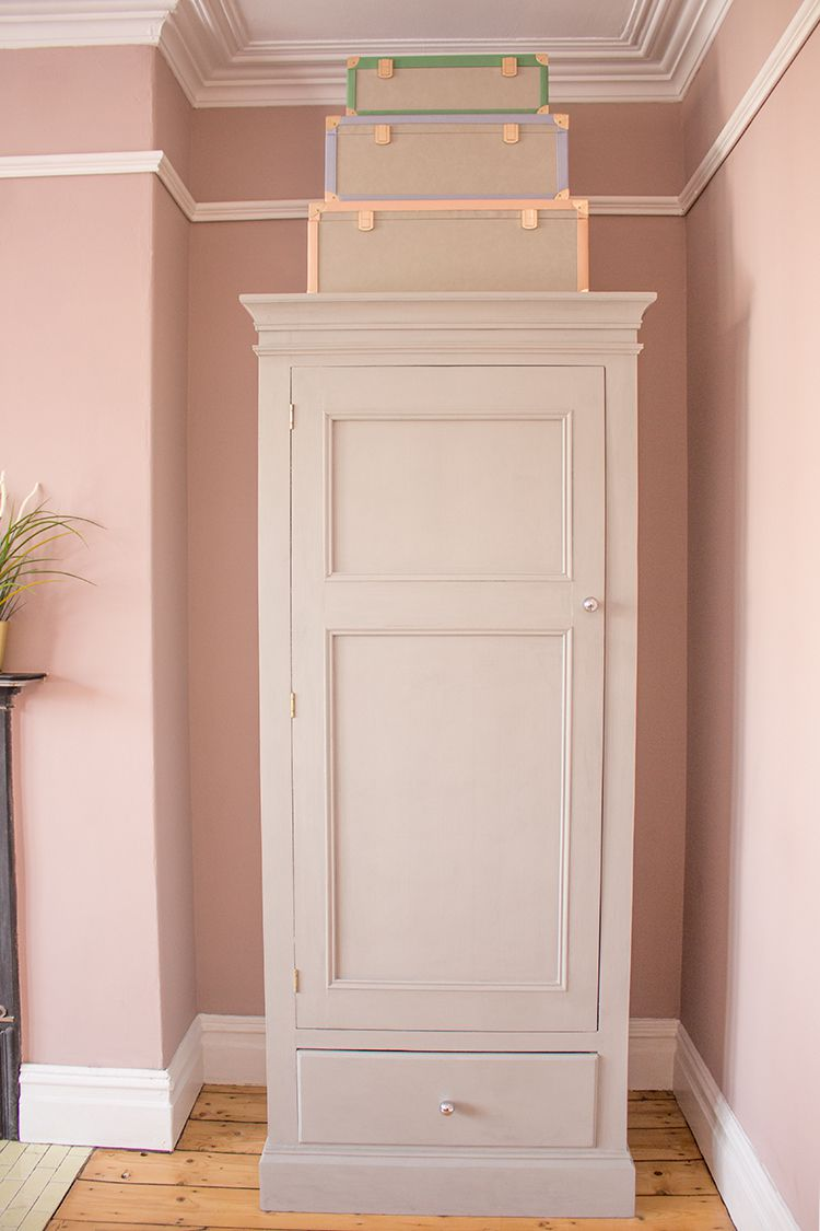 A photo of the wardrobe which has been painted grey, with the colourful storage trunks on top.