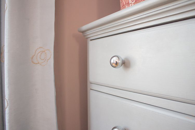 A close up of the chest of drawers which have been painted grey, and new handles added.