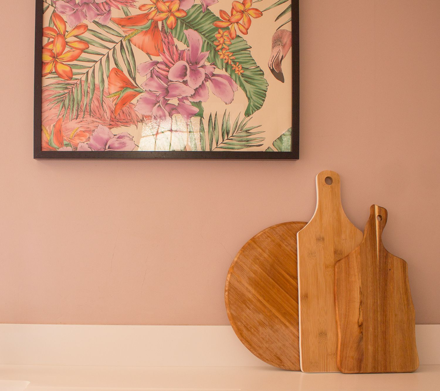 A close up some chopping boards leaning against the worktop and the pink walls.