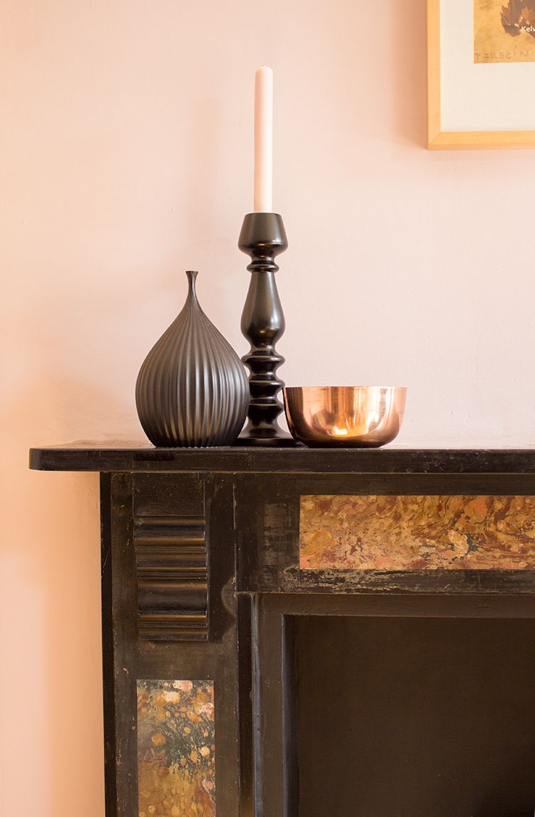 A close up of the mantle piece with a black vase, black candlestick and a copper bowl on top.