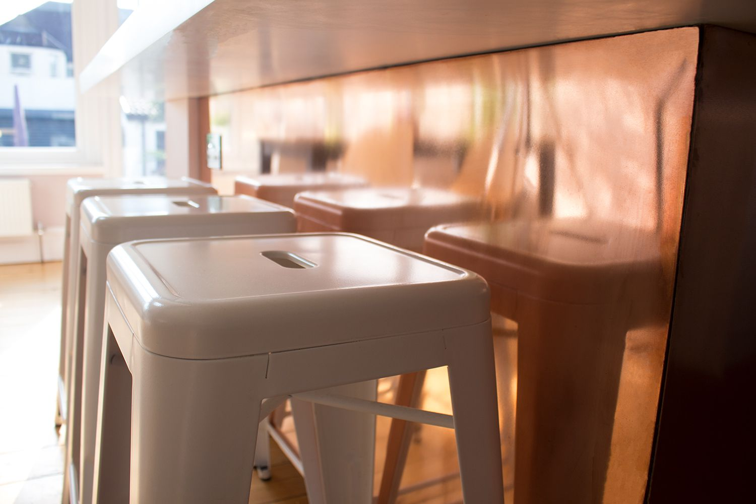 A close up of the new white bar stools against the copper on the back of the kitchen units.