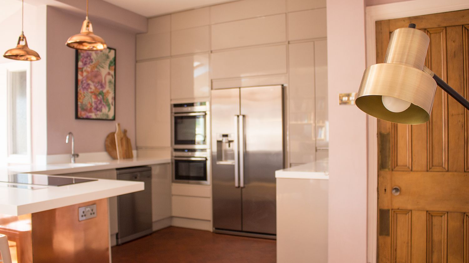 A photo of the kitchen area with light grey cabinets, white Corian worktops and a floor lamp in the foreground.