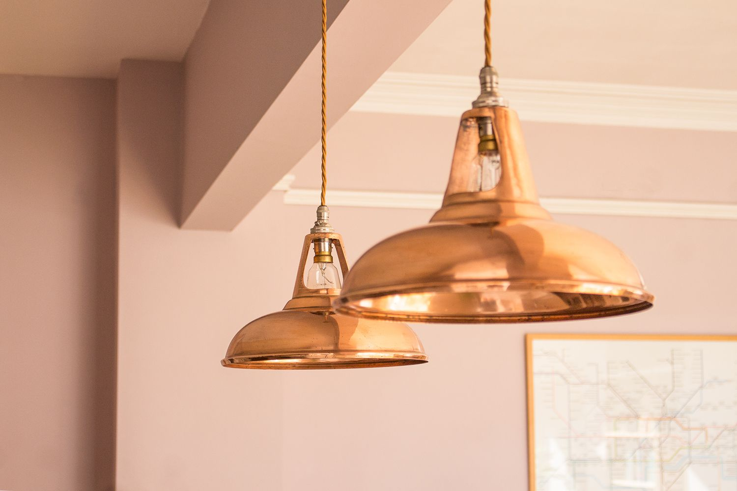 A close up of the two copper pendant lamps which hang over the hob area.
