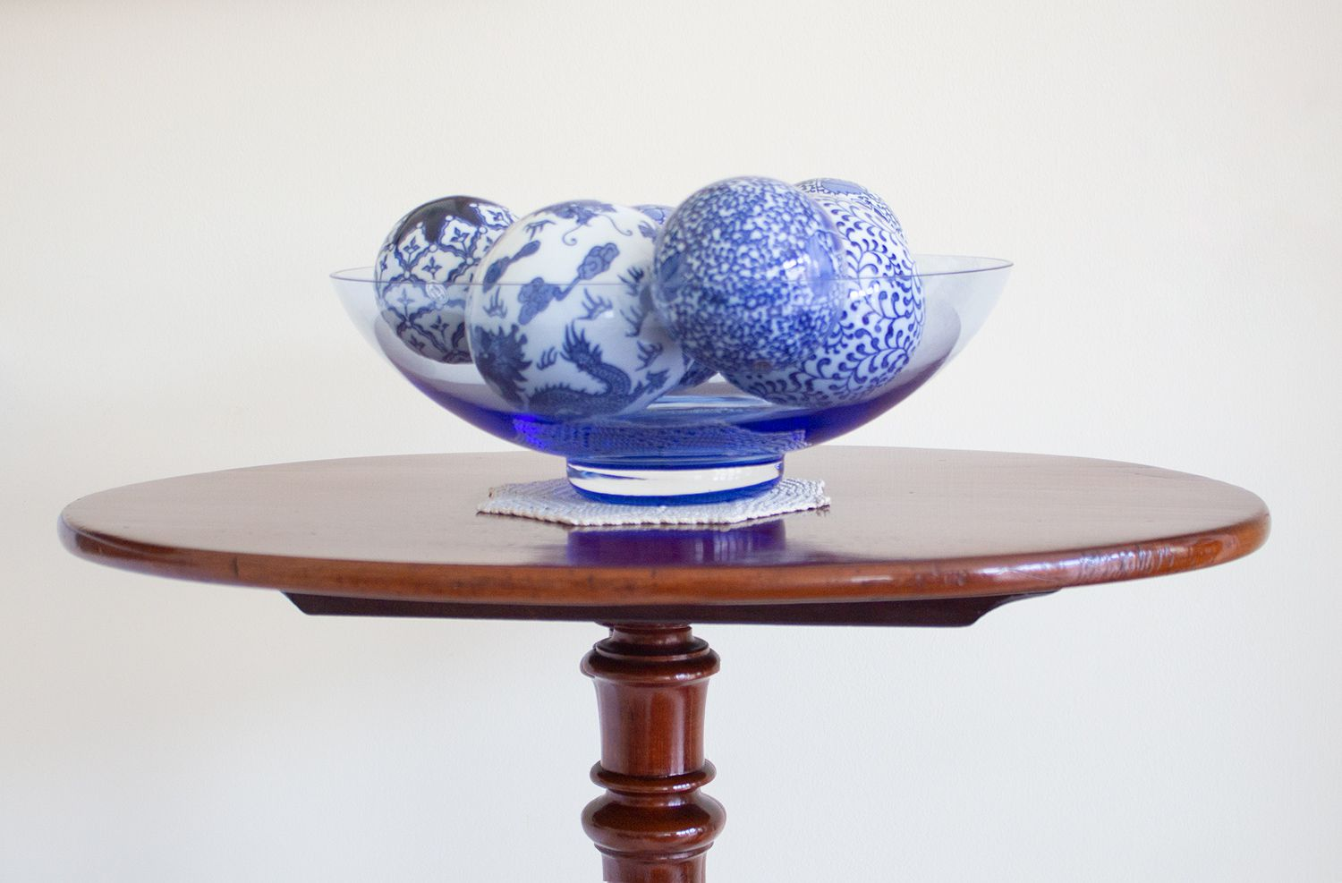 A close up of a blue glass bowl on an an antique table.