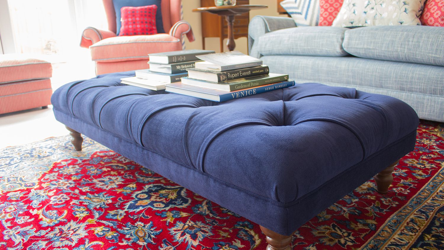 A close up photo of the blue upholstered footstool on the red Persian rug.