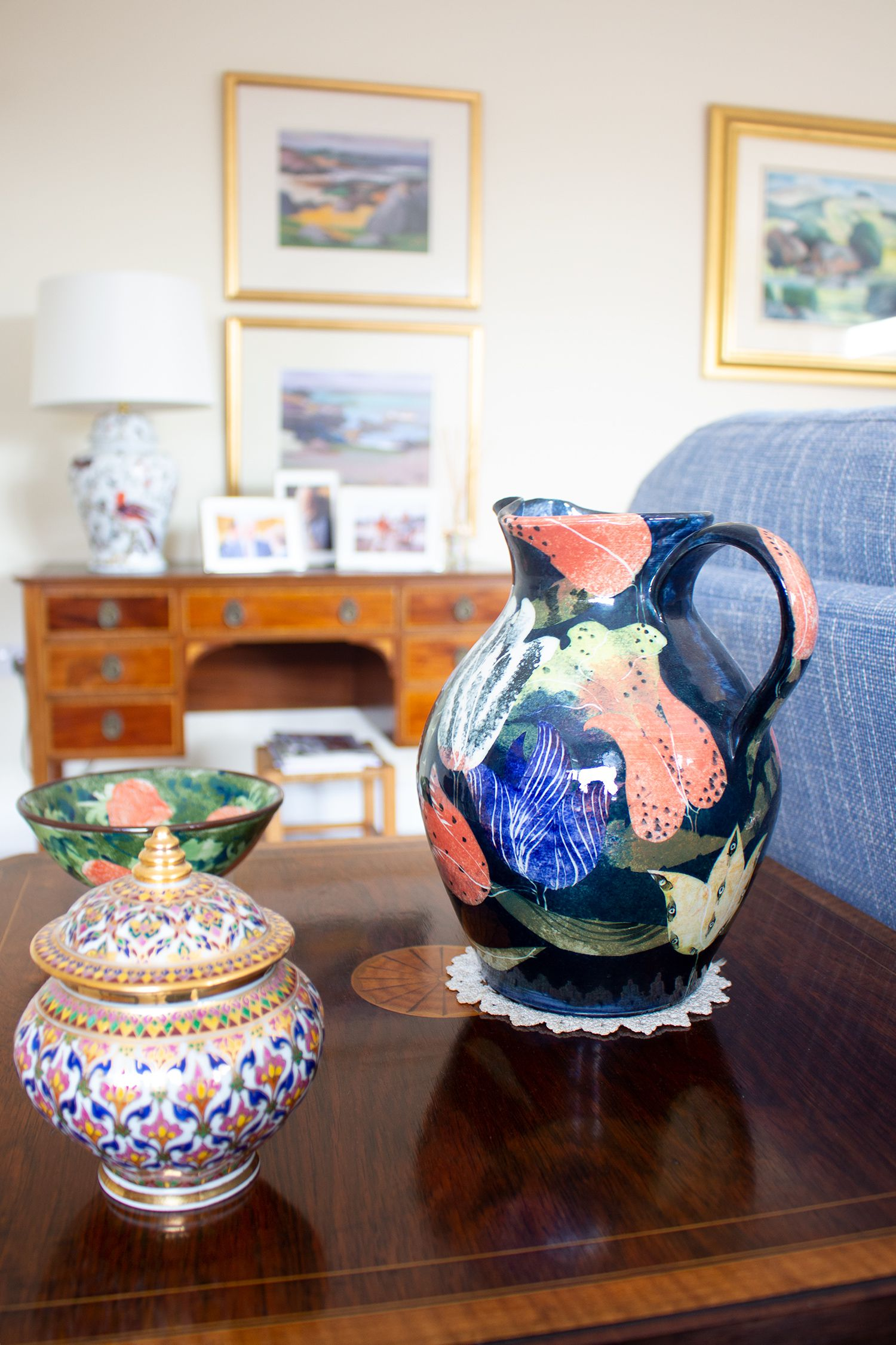 A close up of a colourful blue and red painted jug, on an end table behind the newly upholstered sofa.