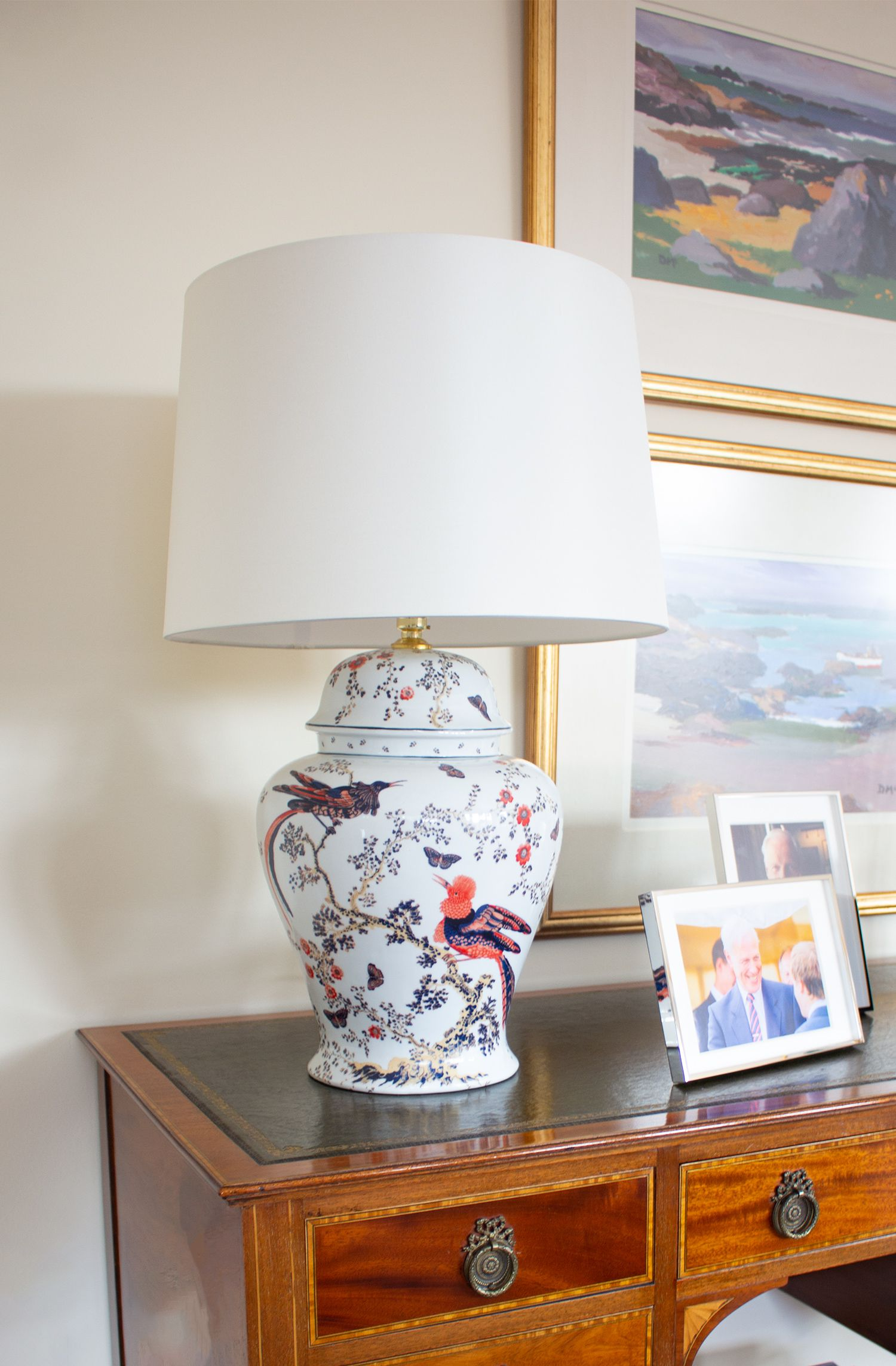 A photo of another hand painted lamp on an antique desk.