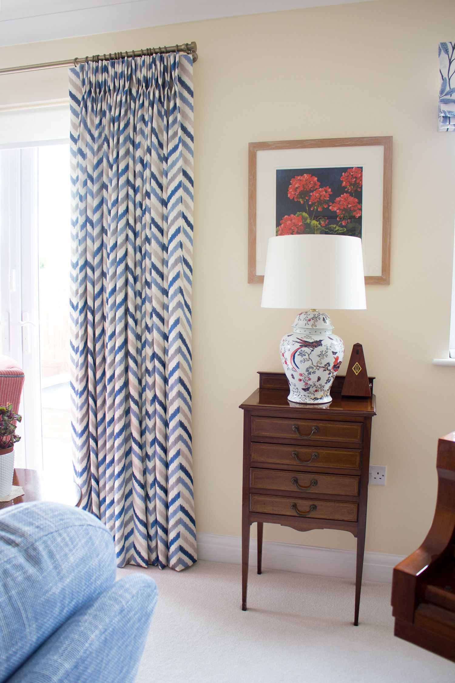 A photo showing one of the new curtains with an antique side table and new hand painted lamp.