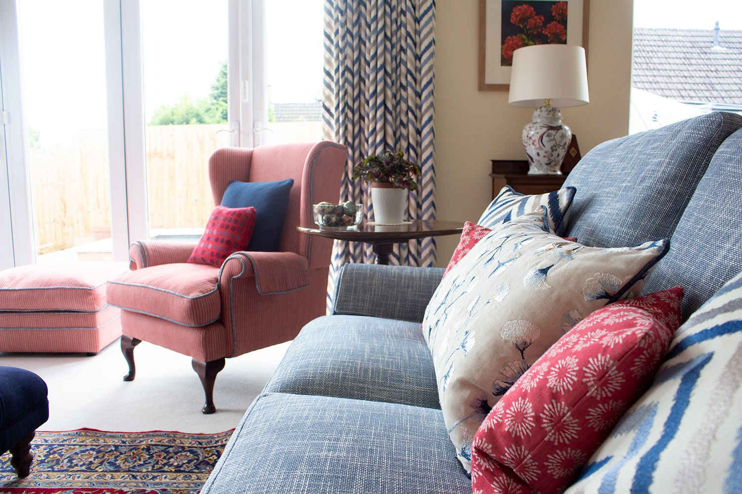 A view along the newly upholstered sofa to the wing chair, showing the red and blue cushions and the new curtains in the background.